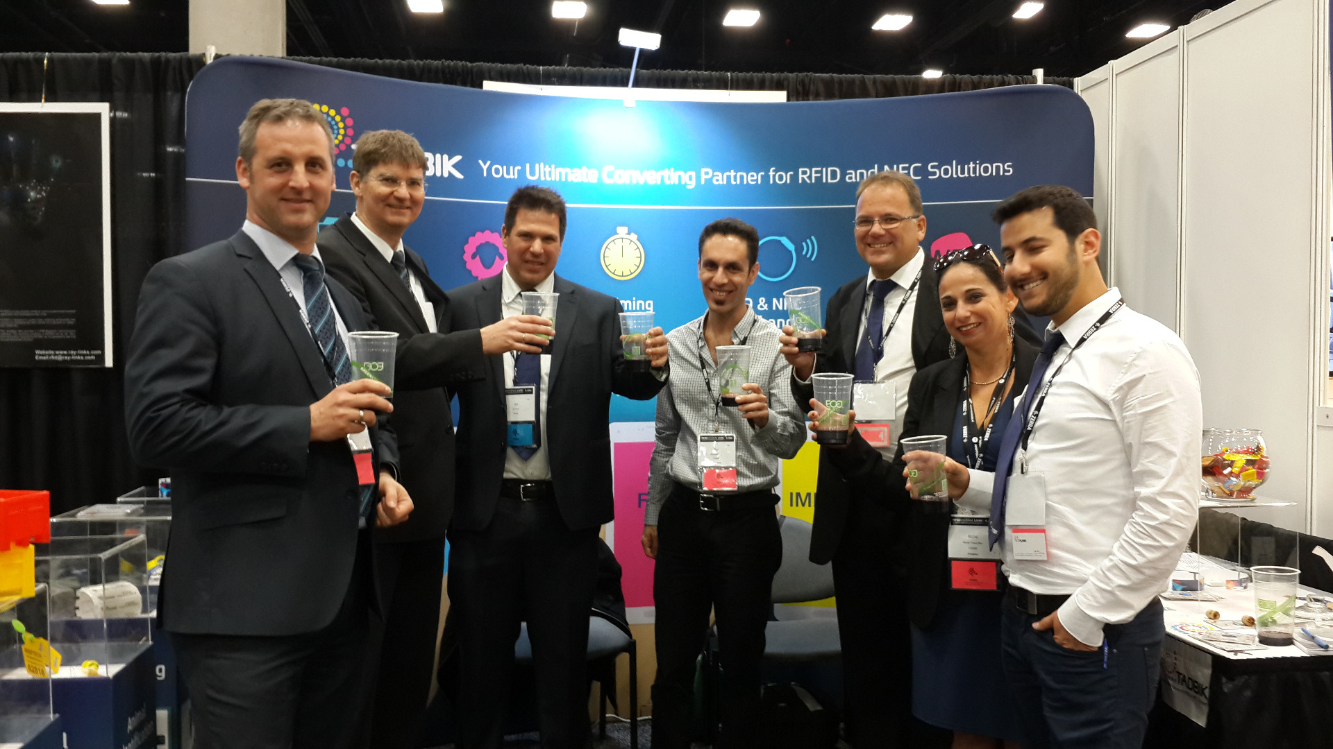 Raising a toast at the RFID Journal Live! 2015 in San Diego. From left: Martin Müller (Sales Manager RFID, Mühlbauer), Thomas Betz (Managing Director, Mühlbauer), Gili Drori (CEO, Tadbik), Guy Goldberg (CTO, Tadbik), Greg Galanakis (RFID Sales Africa, Tadbik), Michal Yanuv Max (Sales And Marketing Director, Tadbik), Idan Uliel (Electronic Segment Leader, Tadbik).